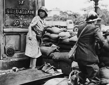 A French man and woman fight with captured German weapons as both civilians and members of the French Forces of the Interior took the fight to the Germans, in Paris in August of 1944.jpg