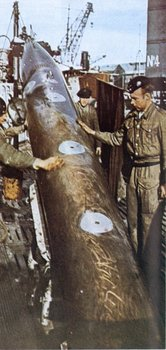 A German submarine crew loading a torpedo into their sub.jpg
