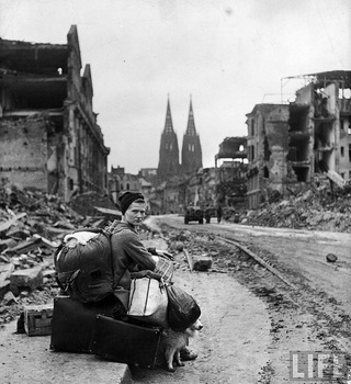 Homeless refugee German woman sitting w. all her worldly possesions on the side of a muddy street amid ruins of Köln, Germany 1945.jpg