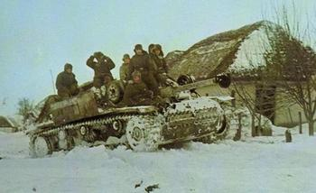 StuG III with mounted infantry securing a Russian village, winter.jpg